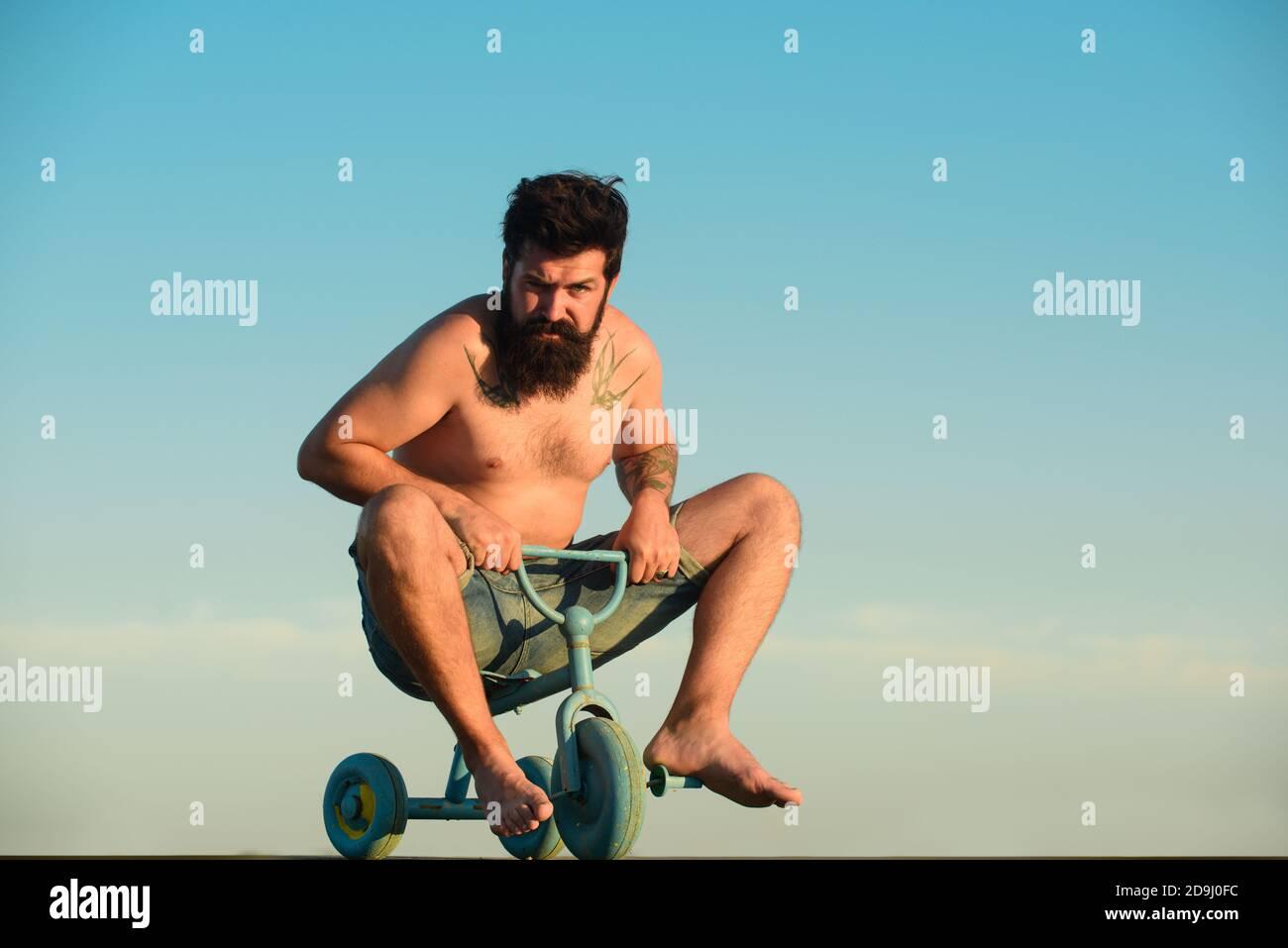 Drôle d'homme sur un vélo. Un homme fou et émotif sur un vélo pour enfants. Un fou qui fait du vélo. Banque D'Images