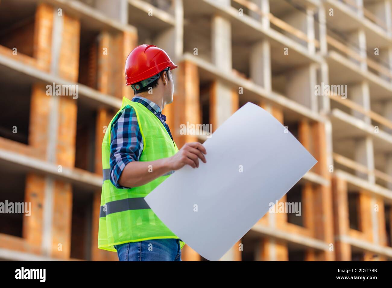Gros plan des ingénieurs travaillant sur un chantier de construction tenant un modèles Banque D'Images