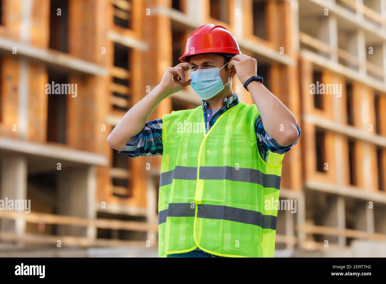 Ingénieur en casque de protection et masque médical sur le chantier de construction au cours de l'épidémie de coronavirus Banque D'Images