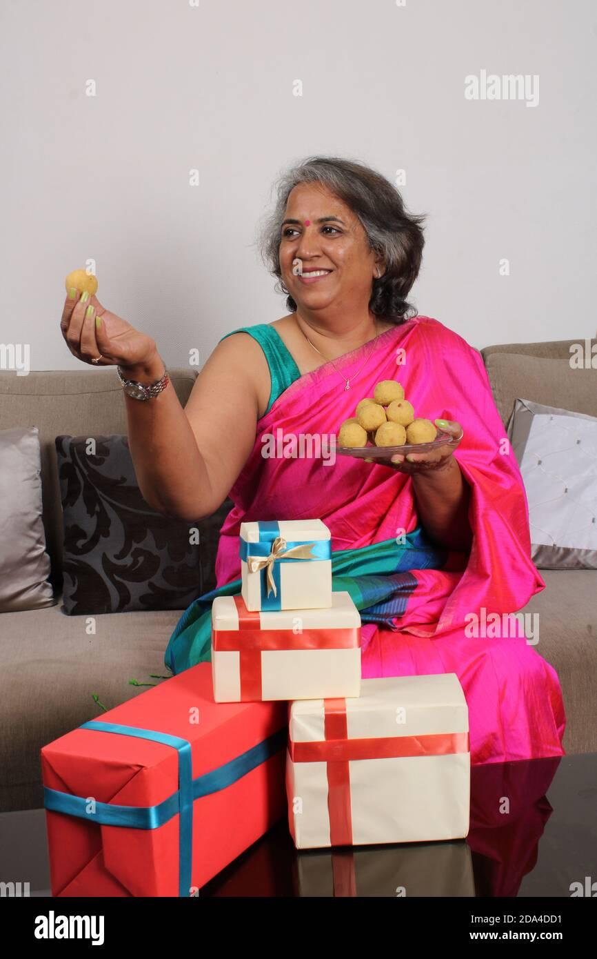 Femme indienne en saree / sari avec laddu et des boîtes cadeaux sur diwali / festival. Banque D'Images