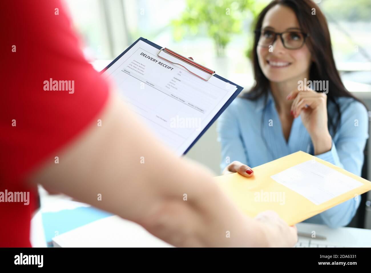Le service de messagerie livre le courrier à une femme d'affaires à son bureau Banque D'Images