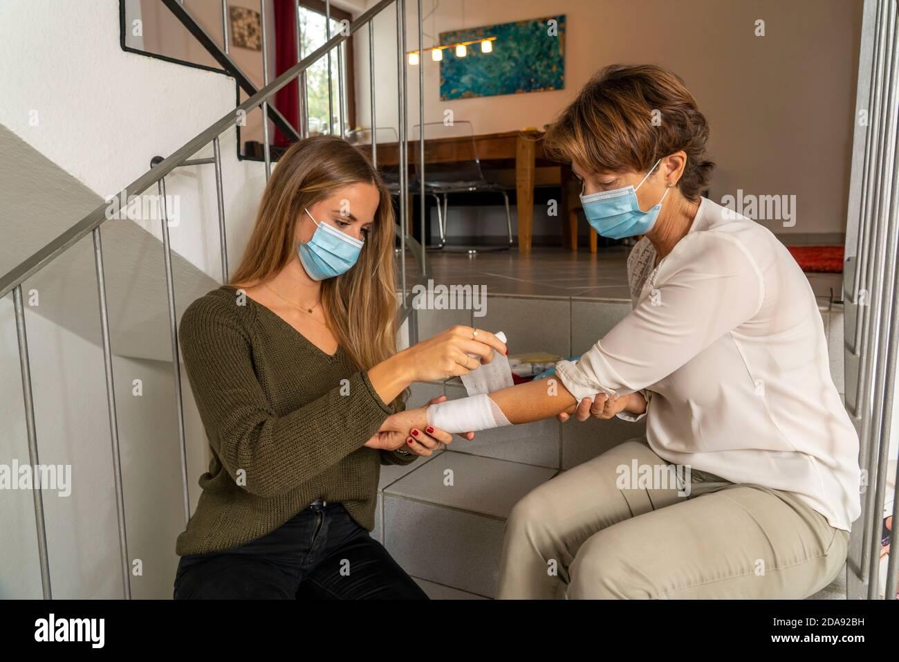 Premiers soins dans des conditions de corona, application d'un bandage, après un accident à la maison, avec un masque de nez et de bouche, lors de l'octroi de premiers soins Banque D'Images