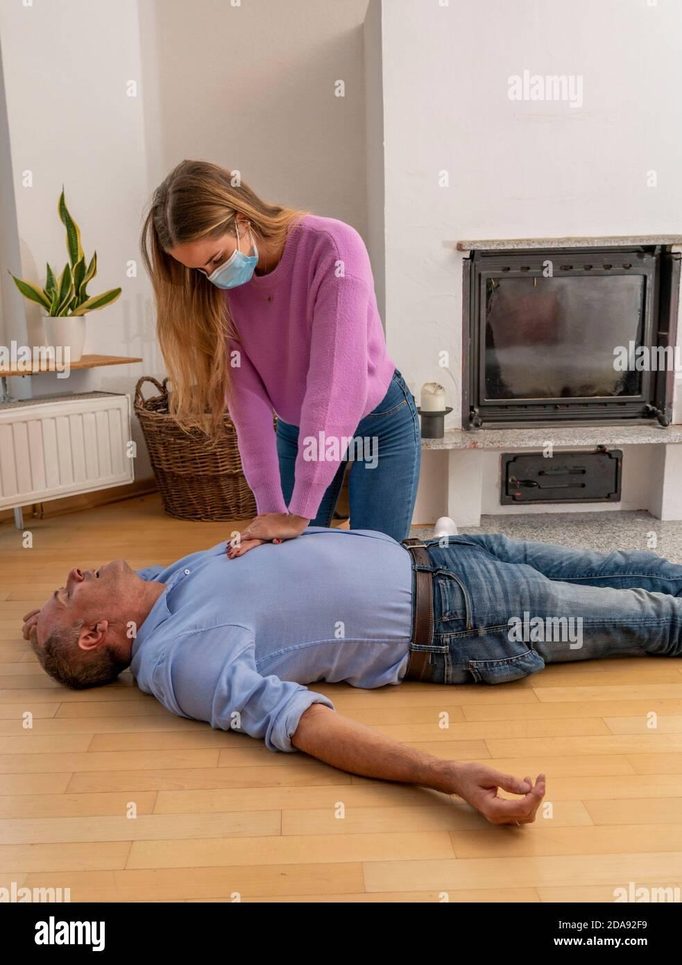 Premiers soins dans des conditions de corona, réanimation, réanimation, massage de pression cardiaque avec masque de bouche et de nez, pour les premiers aidres, symboli Banque D'Images