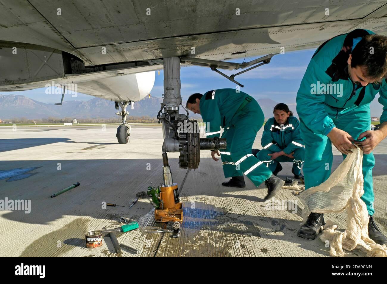 Des mécaniciens réparent un avion sur la piste de l'aéroport international de mère Theresa, Tirana, Albanie Banque D'Images