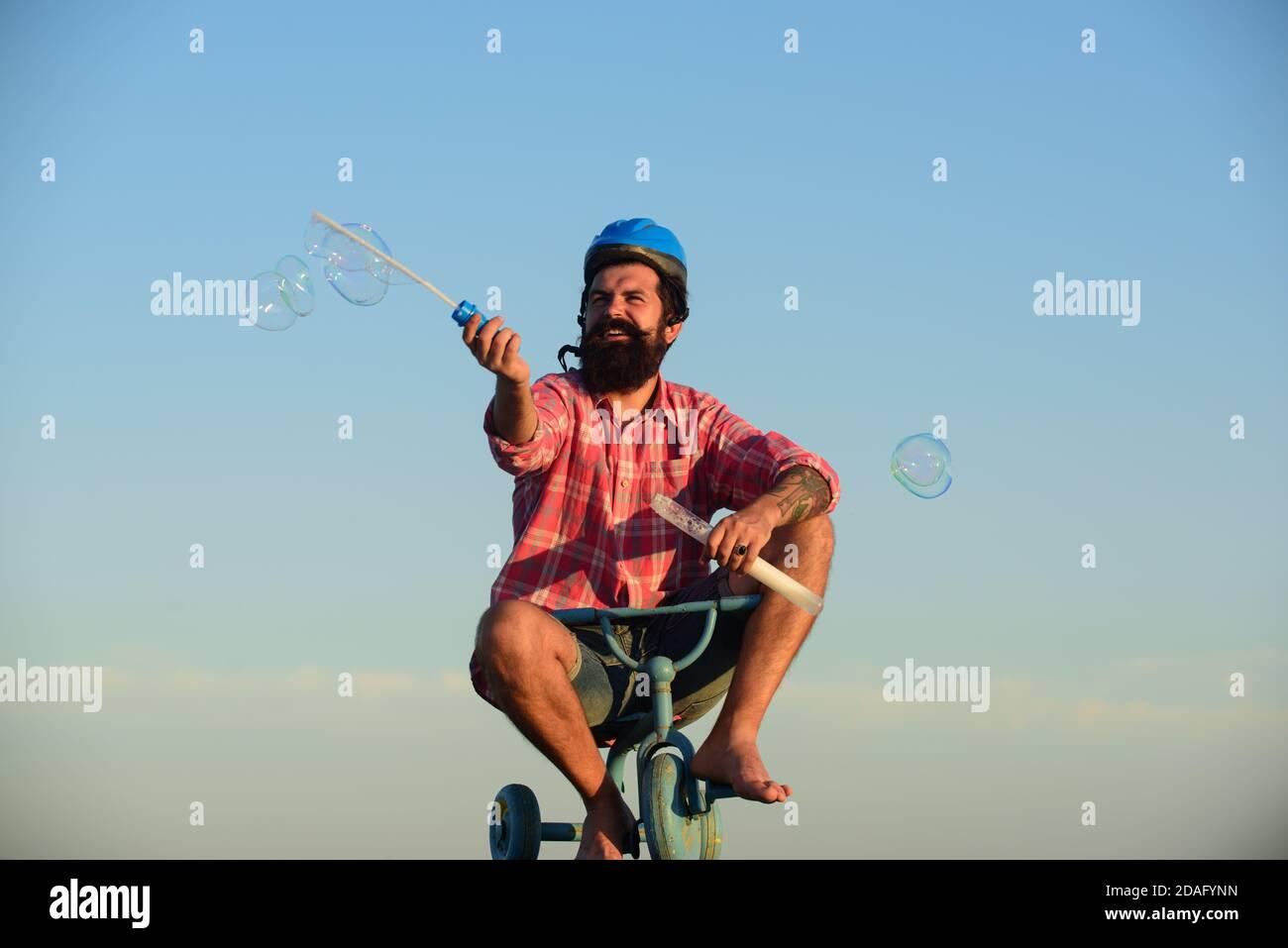 Mémoire d'enfance. Drôle d'homme sur un vélo pour enfants. Vélo nerdy. Banque D'Images