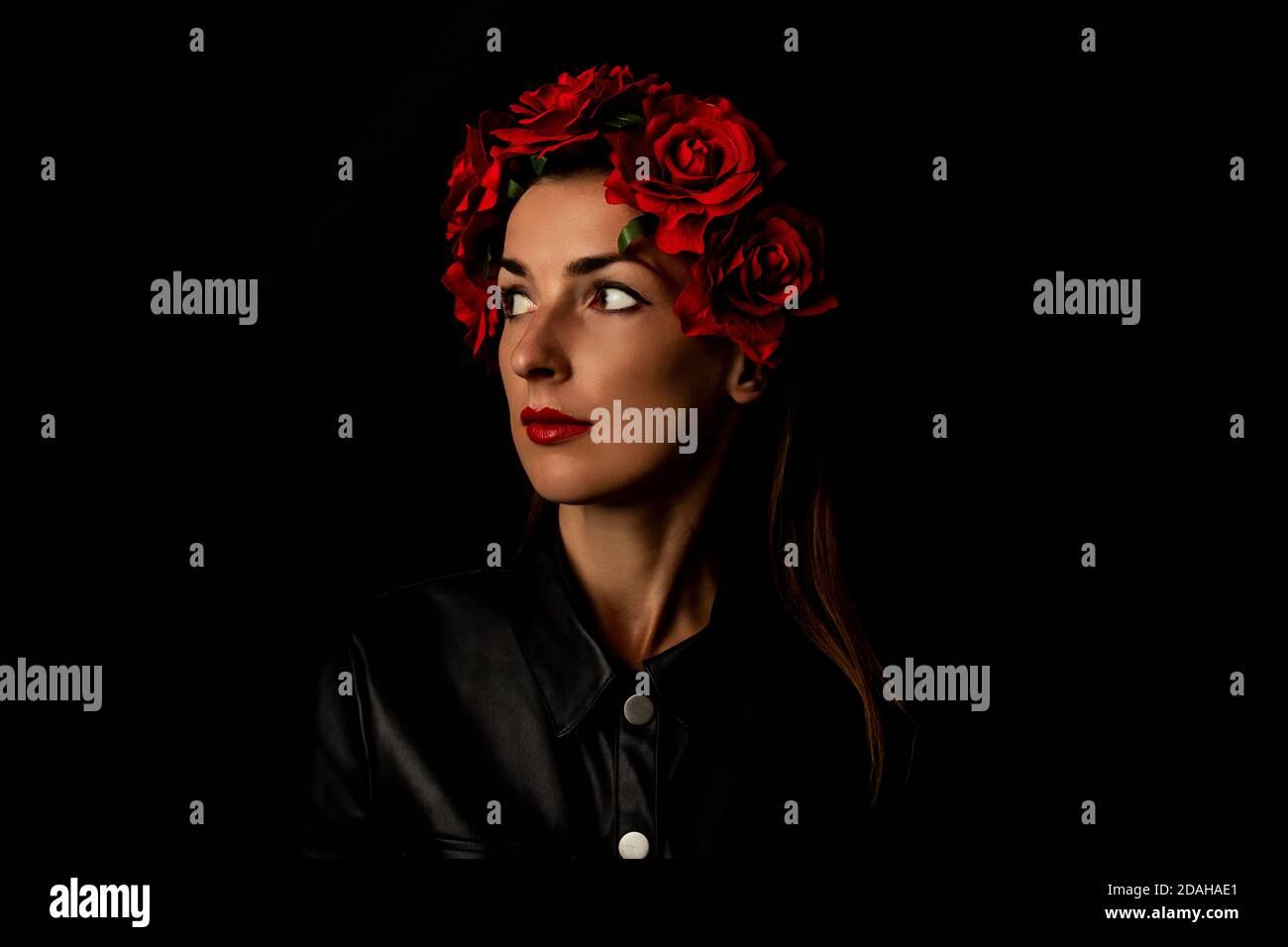 Jeune femme pensive dans une couronne de fleurs rouges sur fond noir. Banque D'Images