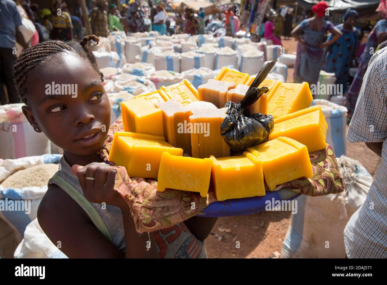 Selingue, Mali, 25 avril 2015; Omou Toure, 10 ans, en 6e année, vendant du savon pour sa mère. Elle va à l'école le matin et vend l'après-midi. Elle peut faire jusqu'à 15,000 CFA par semaine. Banque D'Images