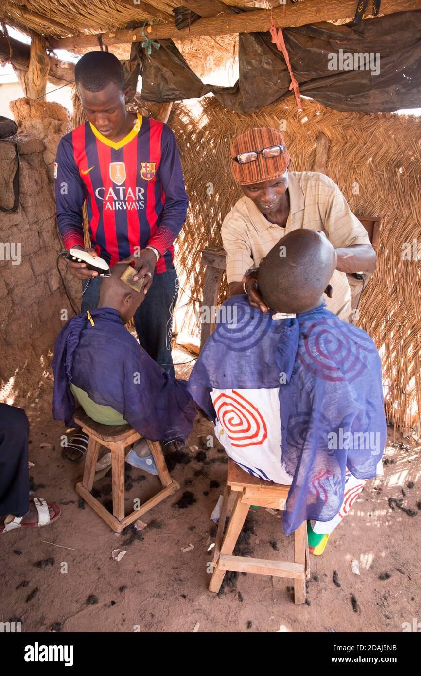 Selingue, Mali, le 25 avril 2015; Barber Boureima Bakayoko, 49 ans, est également un constructeur immobilier. Il ne coupe les cheveux que les jours du marché. Banque D'Images