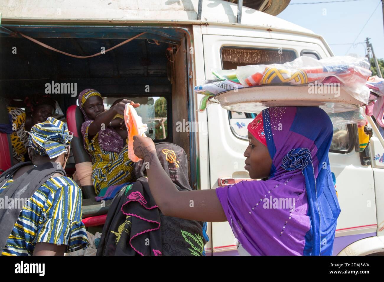 Selingue, Mali, le 25 avril 2015; UNE fille qui vend des sous-vêtements aux passagers d'autobus à la fin du marché. Banque D'Images