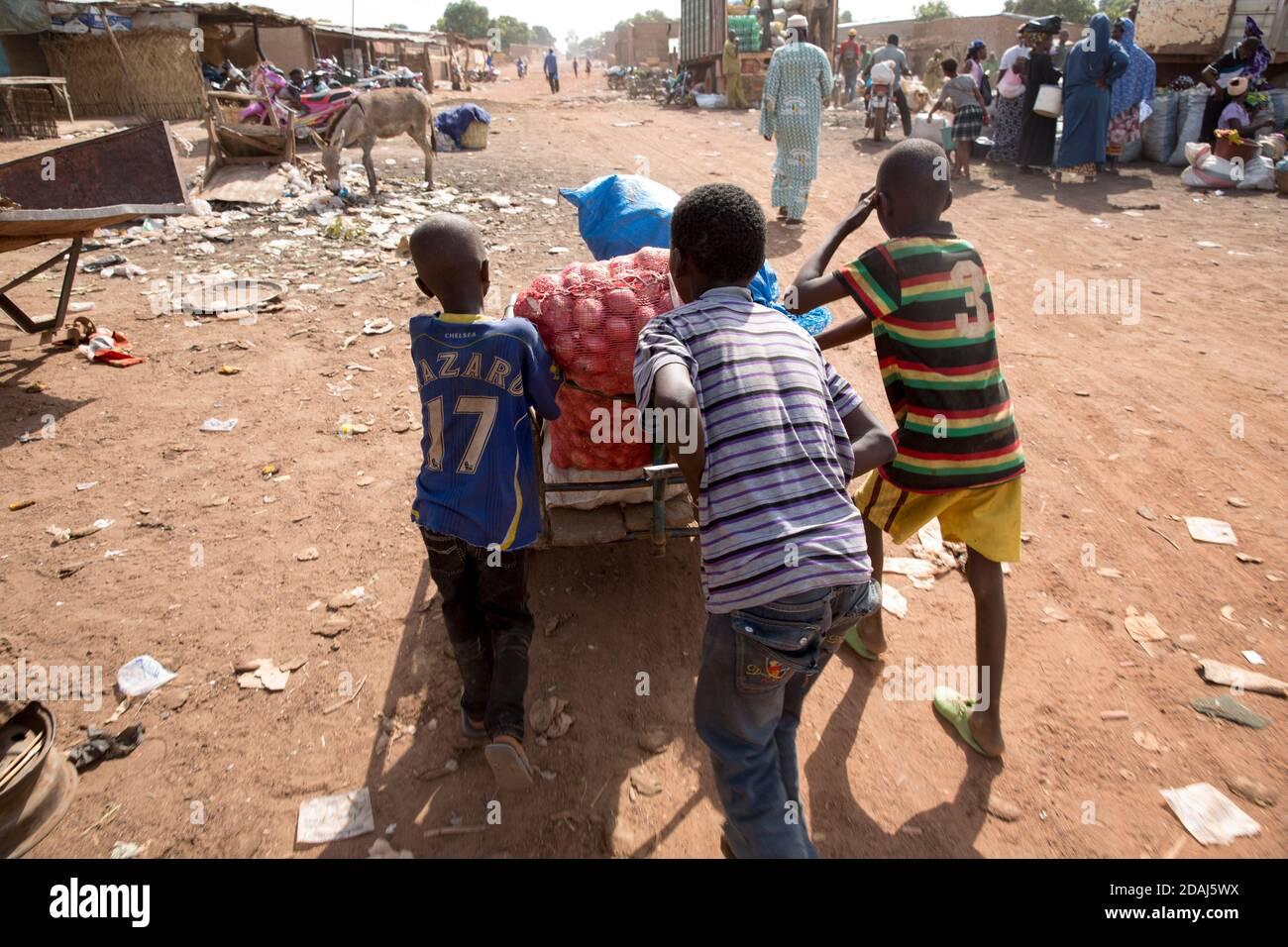 Selingue, Mali, 25 avril 2015; garçons portant des oignons et autres produits à un camion dans la zone de marché le jour du marché. Banque D'Images