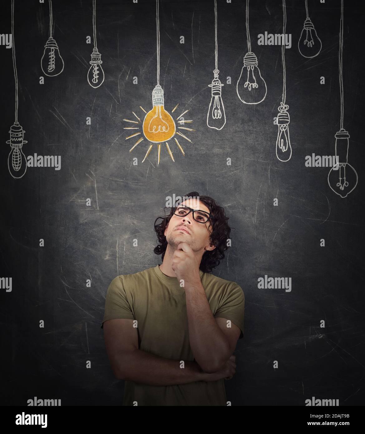 Le jeune homme pensif garde la main sous le menton, geste réfléchi, regardant focalisé, pensant aux idées géniales, en choisissant une ampoule incandescente Banque D'Images