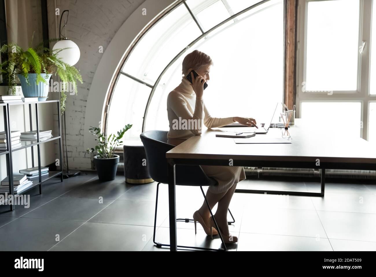 Femme d'affaires confiante parlant au téléphone, assise au bureau Banque D'Images