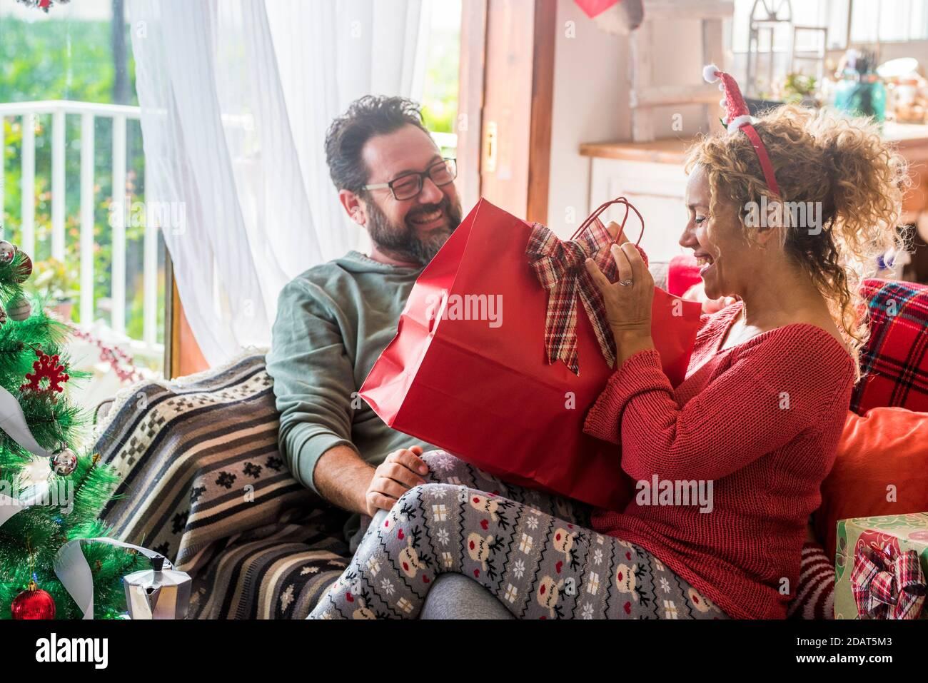 Couple heureux à la maison profiter de la veille de noël ensemble en partageant un cadeau sourire et célébrer la saison des fêtes à la maison - concept de amour et famille partagent des pres Banque D'Images
