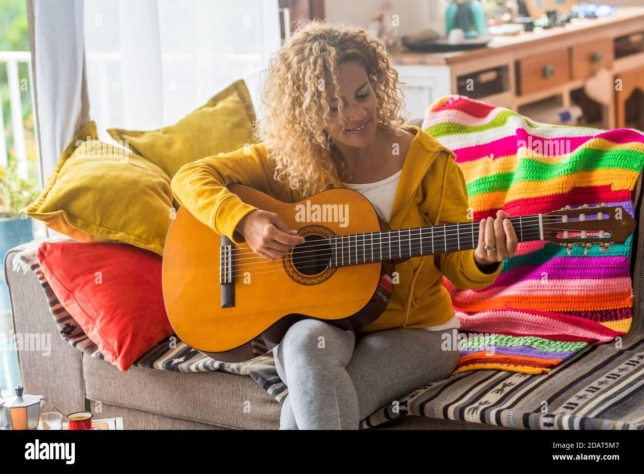 Belle femme d'âge moyen jouer de la guitare à la maison - musique leçon et chanteur assis sur le canapé - les gens jouent instrument et de profiter de chansons et de loisirs Banque D'Images