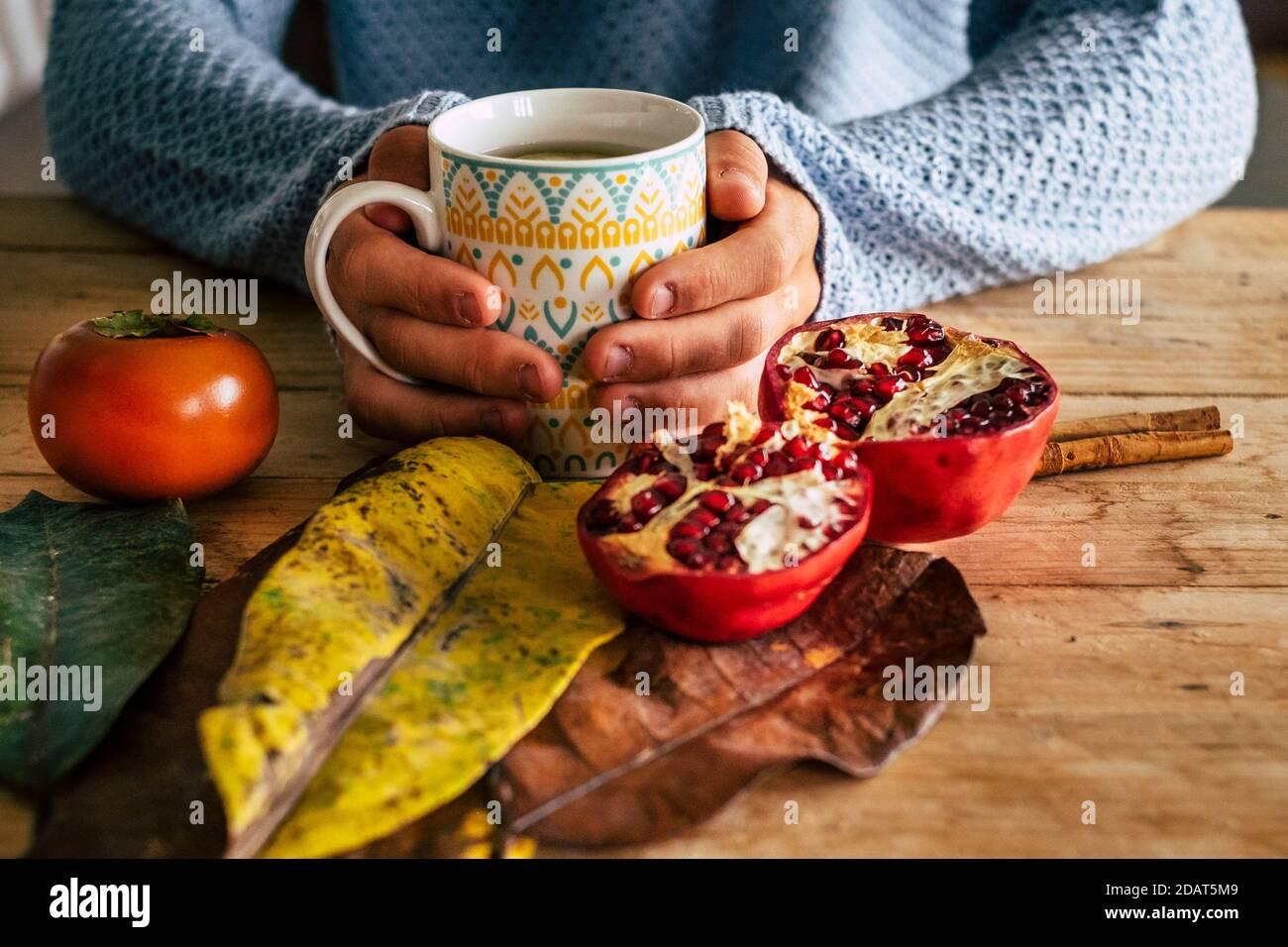 Gros plan de la scène automnale en intérieur avec paire de les mains tiennent une tasse de thé sur un jaune de bois et table orange avec pamplemousse et feuille Banque D'Images