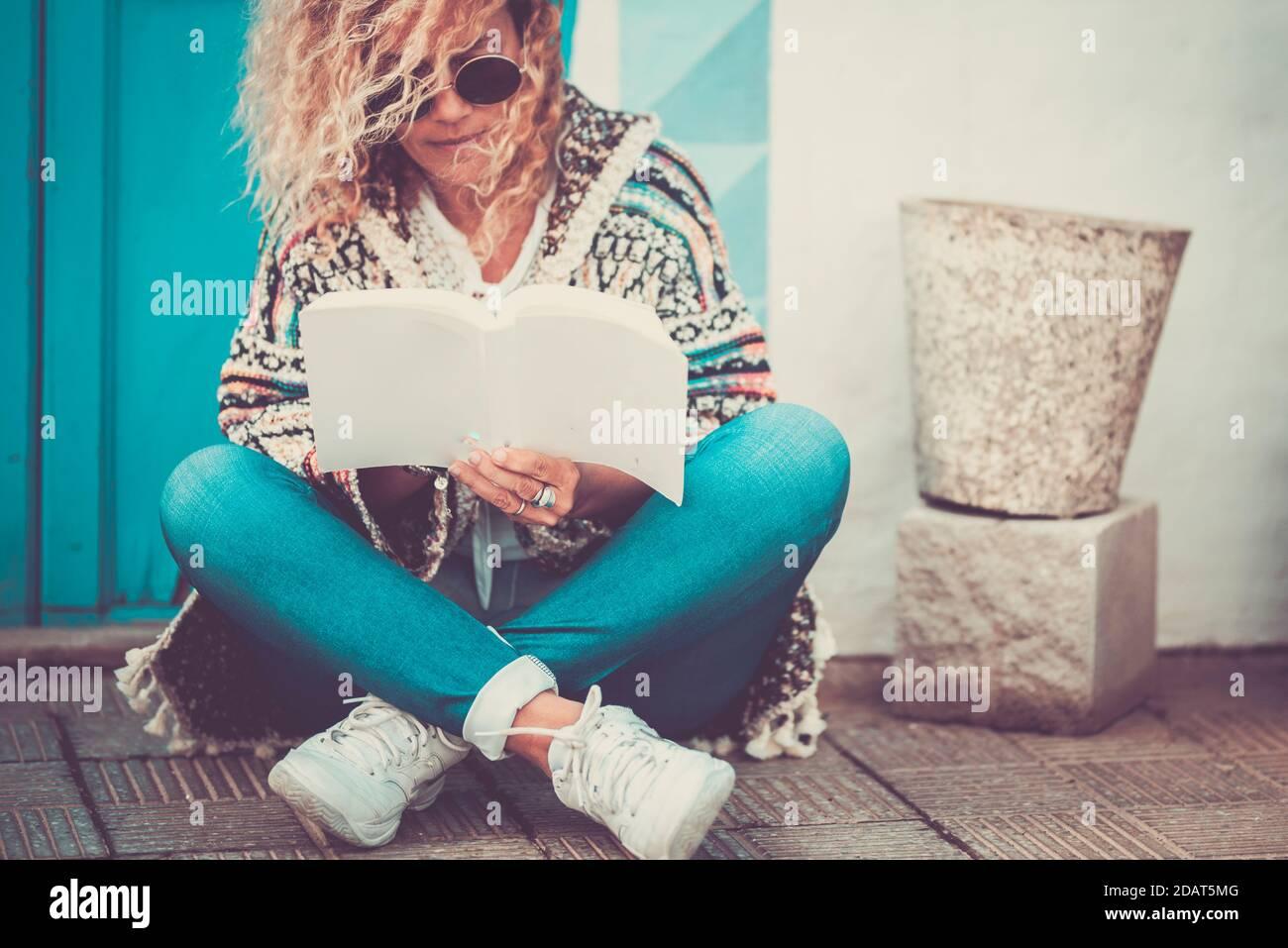 Magnifique portrait de femme assis sur le sol à l'extérieur lire un livre papier ou étudier à l'extérieur de la maison - jeune les adultes lisent et apprennent à profiter du Banque D'Images