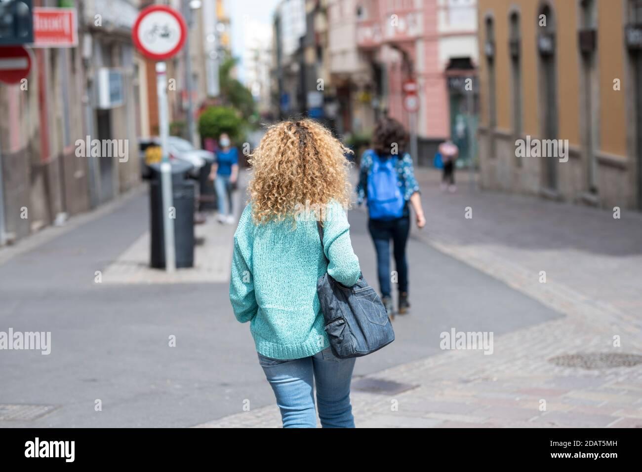 Femme blonde mauriquement vue de marche arrière dans la rue dans la ville - shopping activité de loisirs en ville pour de vraies personnes Banque D'Images