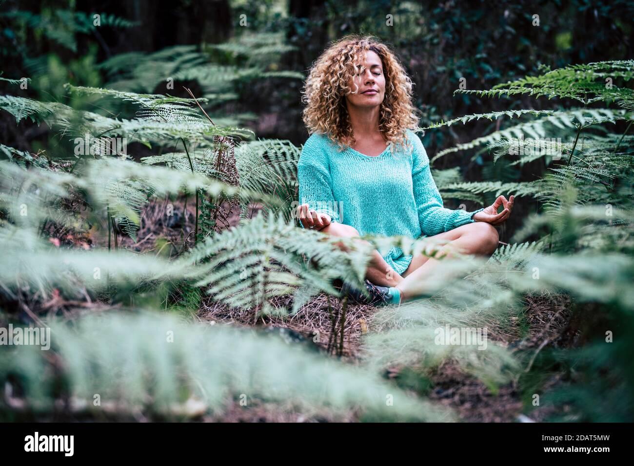 Détendue belle dame ne méditation assis au milieu de nature plante en plein air - les gens en pleine conscience méditent l'activité en appréciant extérieur naturel Banque D'Images