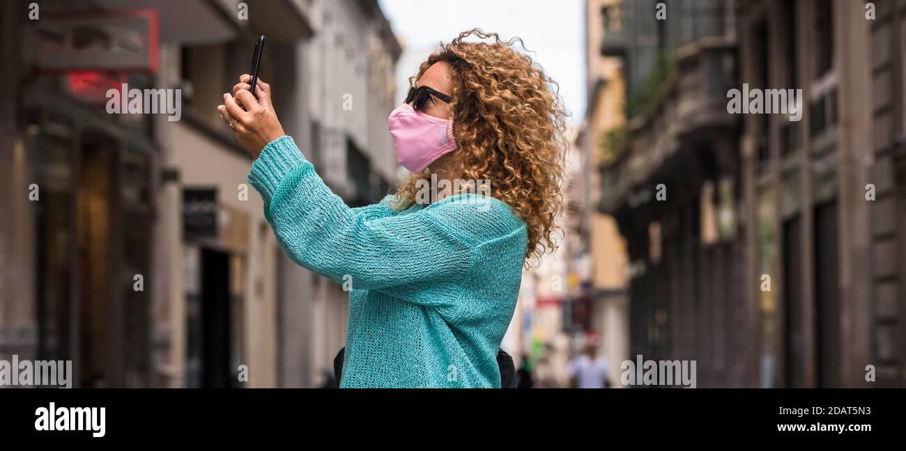 Femme faire appel vidéo de téléphone portant un masque de protection médicale pour coronavirus covid-19 urgence sanitaire dans la ville - les gens marchent et profitez de la ville prote Banque D'Images