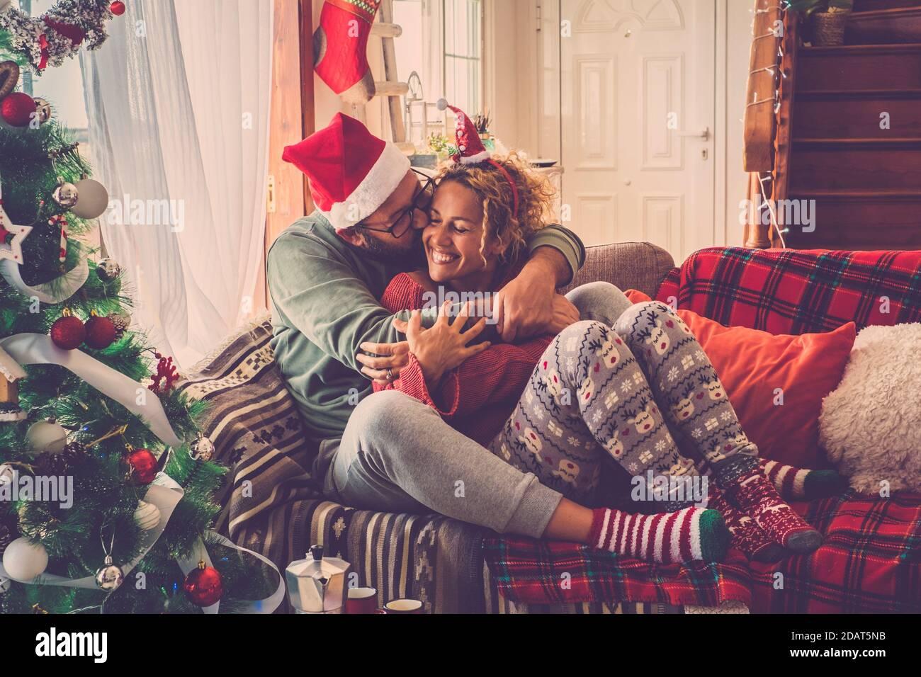 Couple amoureux appréciez et célébrez la veille de noël matin à maison embrassant et embrassant s'asseoir sur un coloré et canapé décoré à la maison - vin de vacances Banque D'Images