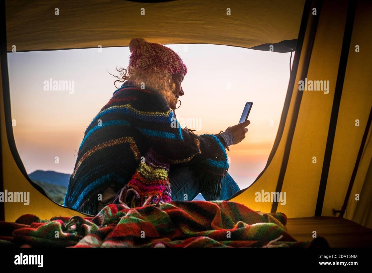 Liberté et aventure voyage vacances alternative loisirs activité style de vie avec une femme s'assoit à l'intérieur d'une tente avec des montagnes et le coucher du soleil afficher utiliser smar Banque D'Images