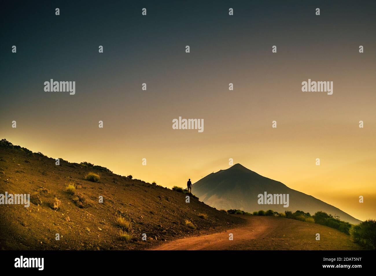 Homme debout avec vue sur les montagnes et coucher de soleil ciel coloré - concept de voyage d'aventure et parc extérieur activité de loisirs pour peopl Banque D'Images