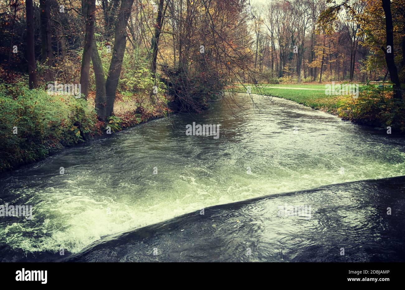 Canal d'eau à Munich Englischer Garten en automne, magnifique parc à l'intérieur le coeur de la ville pour faire une promenade la nature Banque D'Images