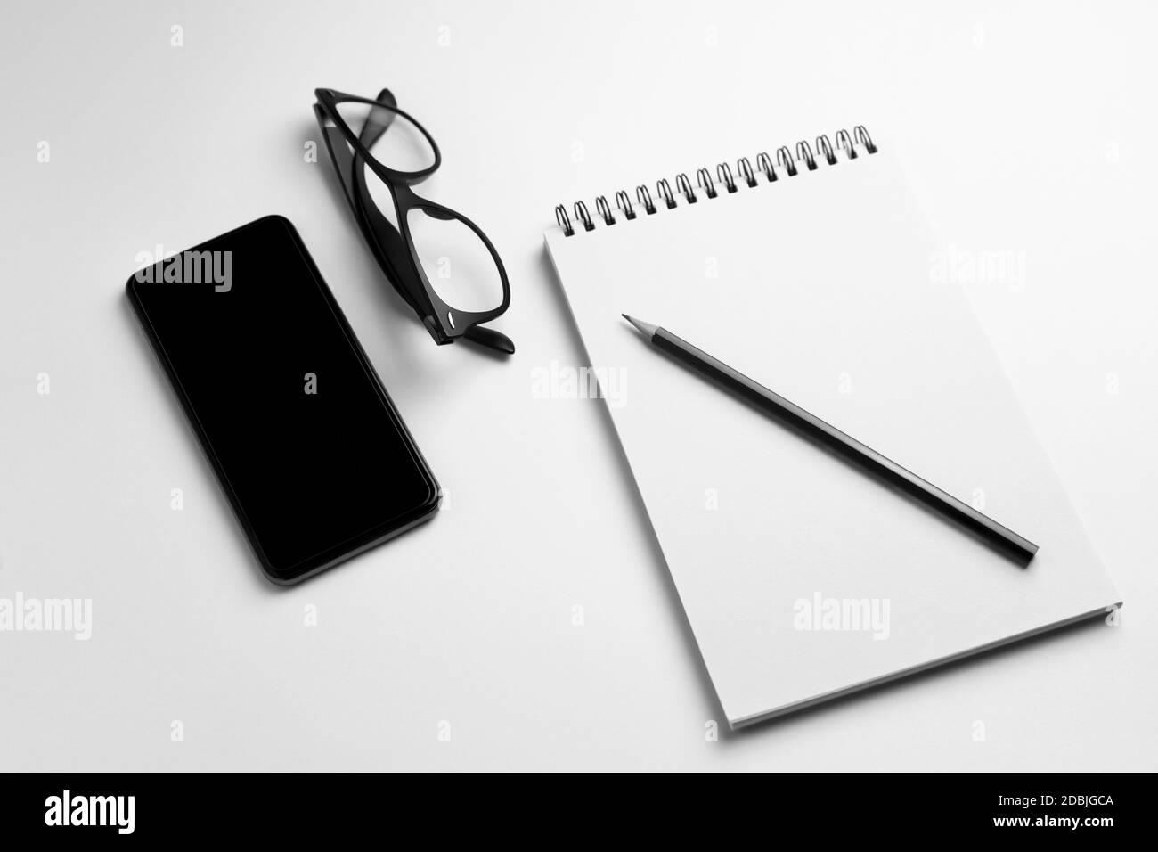 Smartphone avec un ordinateur portable vierge, un crayon et des lunettes sur fond blanc.vue du dessus concept d'entreprise , d'espace de travail et de technologie. Banque D'Images