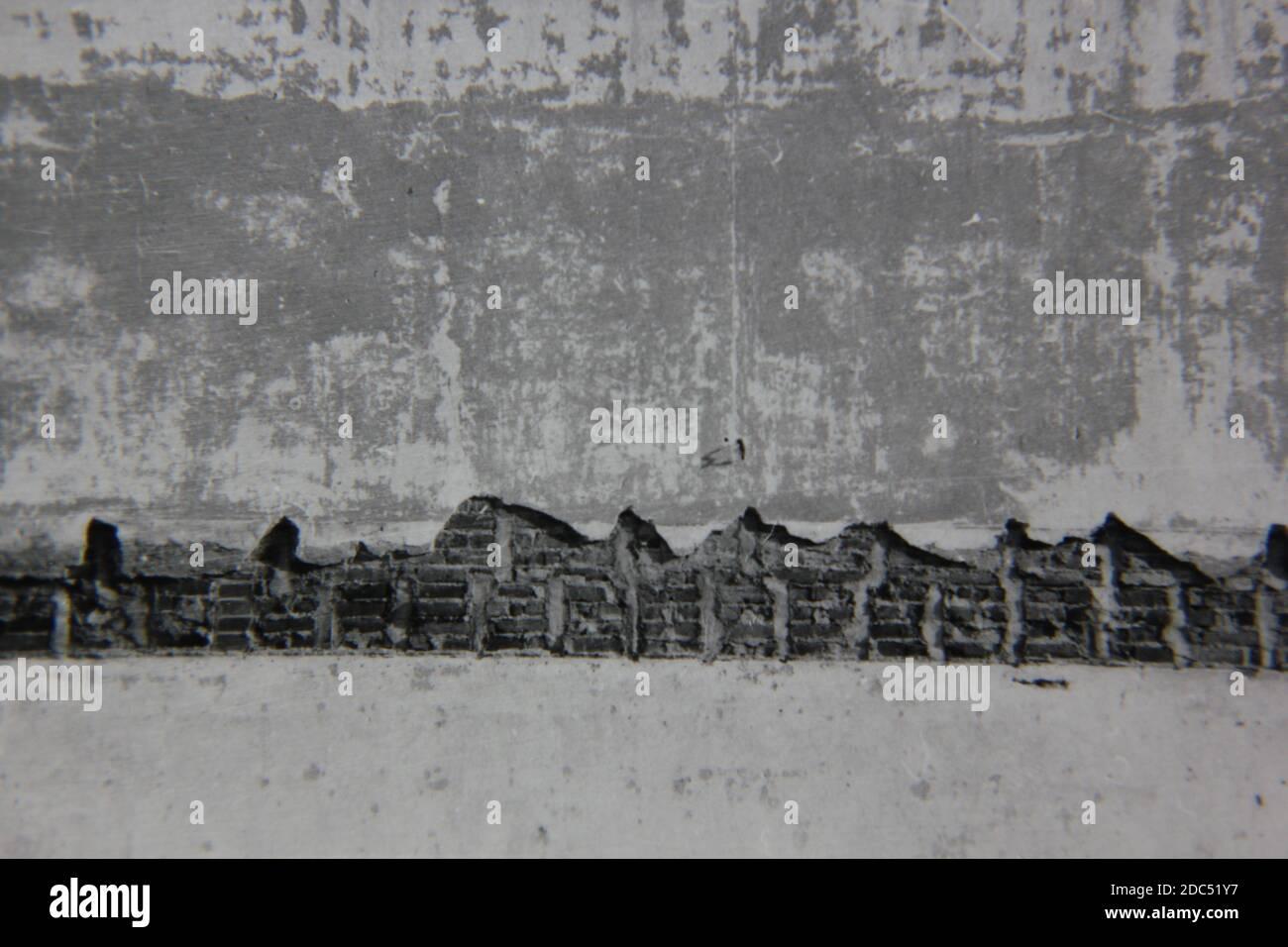 Belle photographie en noir et blanc vintage des années 1970 d'un mur en plâtre qui s'effrite avec une structure en brique. Banque D'Images