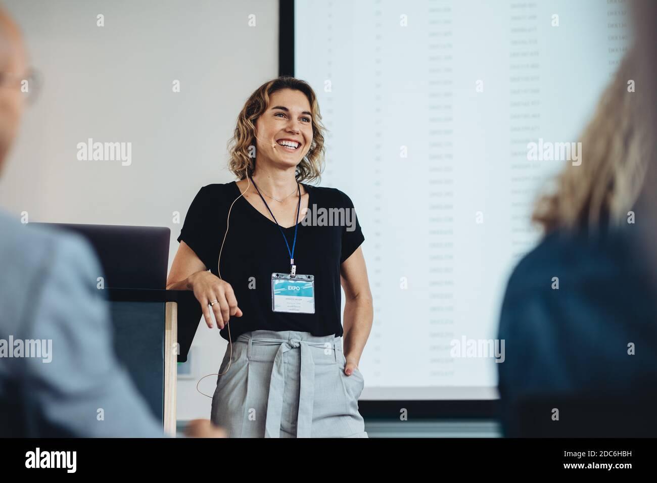 Femme d'affaires souriante qui prononce un discours lors d'une conférence. Présentation professionnelle réussie. Banque D'Images