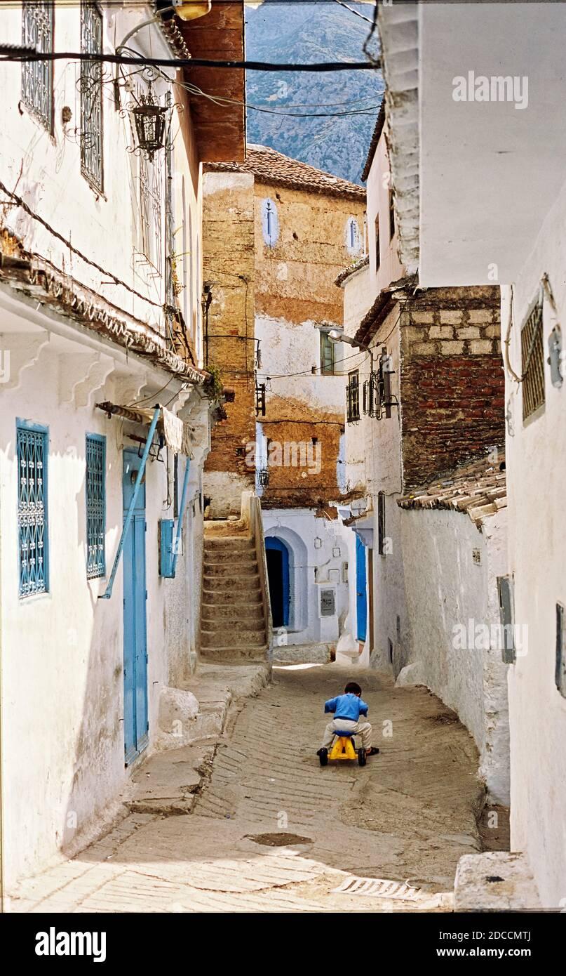 Rues et ruelles de la Médina de Chefchaouen, Maroc. Un enfant joue dans la rue Banque D'Images