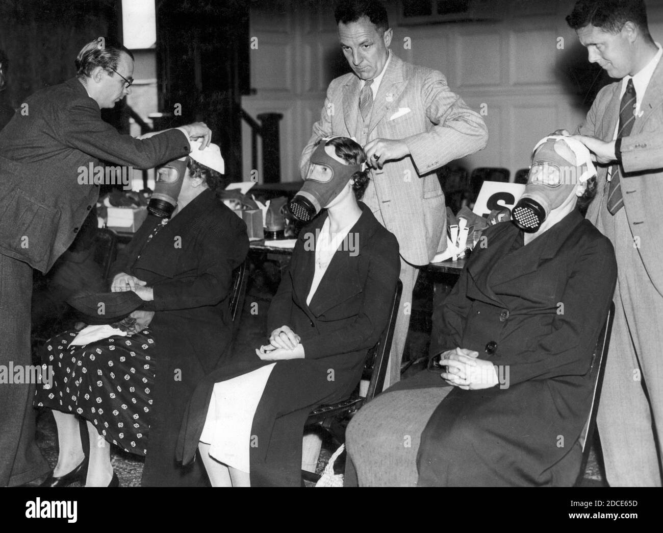 En 1939, trois femmes civiles sont installées pour leur propre masque à gaz personnel. L'Allemagne commençait à mener des actions de type guerre contre ses voisins. Vingt ans plus tôt, la première Guerre mondiale avait montré les horreurs du gaz toxique utilisé comme arme, et en Espagne des années 1930, des civils avaient subi des attaques au gaz par des avions. La Grande-Bretagne a compris qu'une attaque similaire de l'Allemagne serait dévastatrice pour sa population. À la fin de 1939, chaque homme, chaque femme et chaque enfant de Grande-Bretagne se faisait délivrer un masque à gaz. Pour voir mes autres images WW II, recherchez: Prestor vintage WW II Banque D'Images