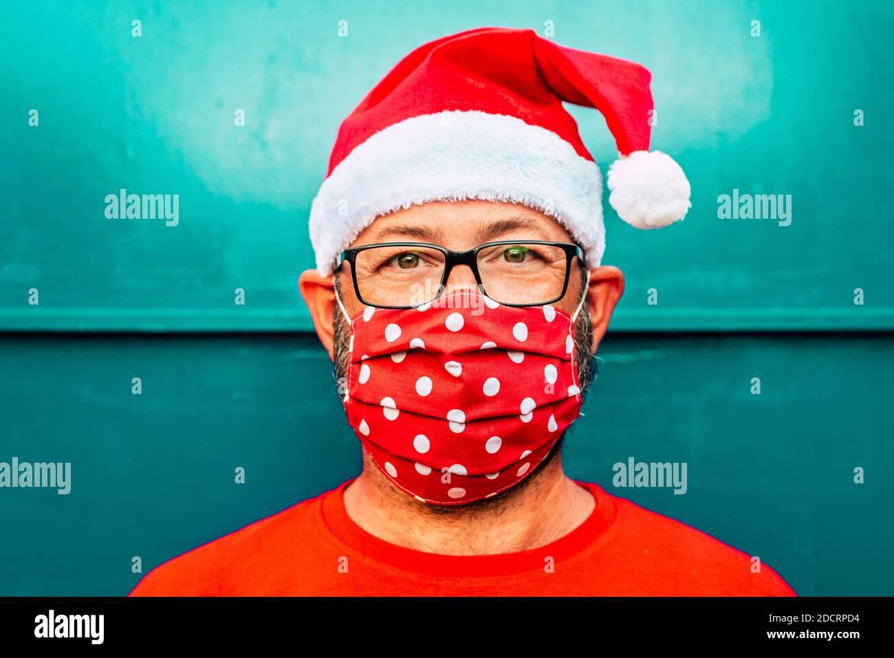 Portrait d'un homme de race blanche adulte portant un masque de protection rouge pour coronavirus vocid-19 et chapeau de chrismtas du père noël - concept de personnes seules pendant ho Banque D'Images