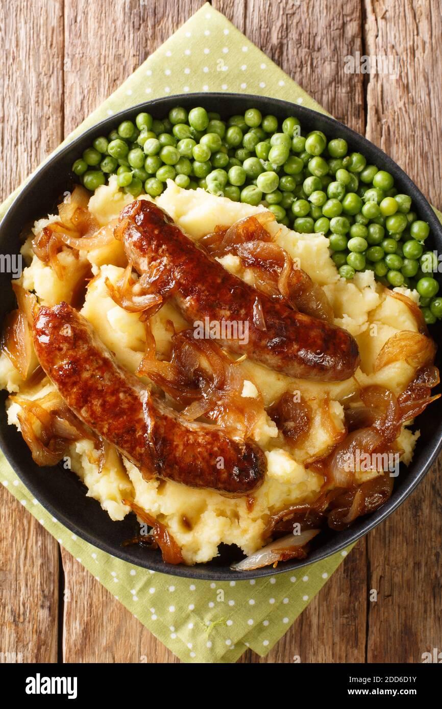 Bangers and Mash with Onion sauce closeup dans l'assiette sur la table. Vue verticale du dessus Banque D'Images