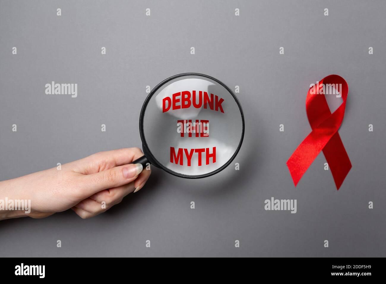 La main d'une femme tient une loupe avec du texte. Ruban rouge sur fond gris. Pose à plat. Le concept de la Journée mondiale du sida. Banque D'Images