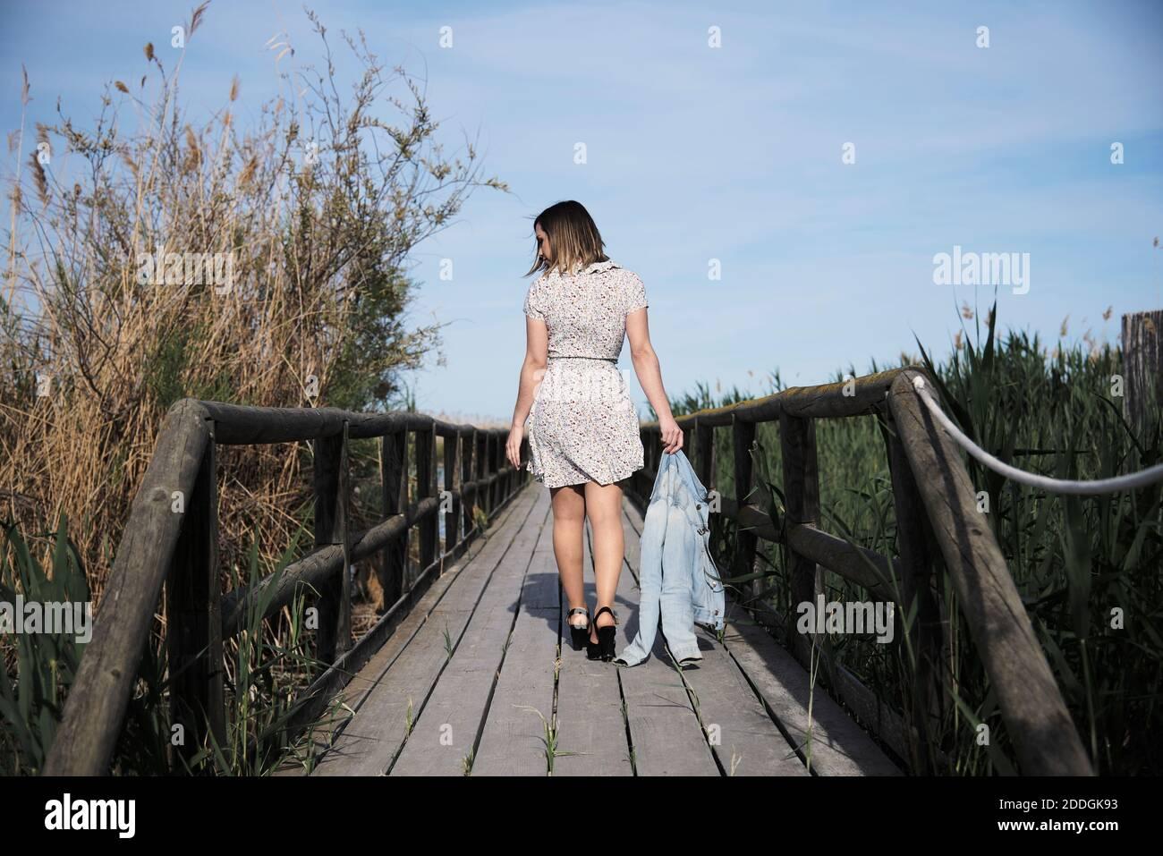 Vue intégrale sur le dos de la jeune femme en robe décontractée avec une veste à la main se promenant sur une passerelle en bois parmi les hauts herbe sèche par beau temps Banque D'Images