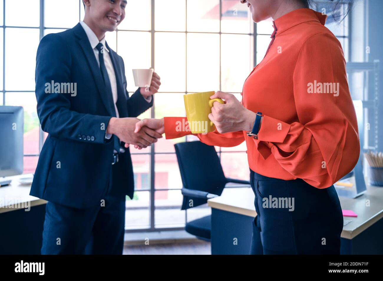 Partenaires commerciaux qui se secouent la main avec une tasse à café. Concept de coopération commerciale. Banque D'Images