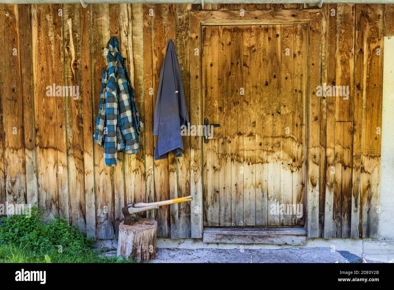 Deux haches en bois coincées dans le coffre à hacher en bois. En arrière-plan, un mur en bois de la maison et deux vêtements de travail accrochés à un crochet. Banque D'Images