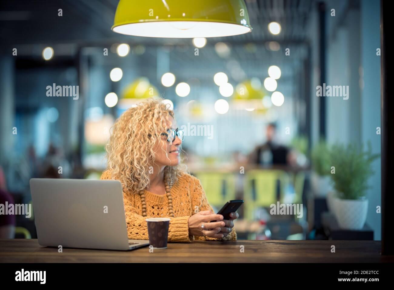 Une jeune femme adulte moderne voyage et travaille avec la technologie de roaming téléphone en ligne et ordinateur portable dans le café de bureau gratuit de l'aéroport porte - personnes et sma Banque D'Images