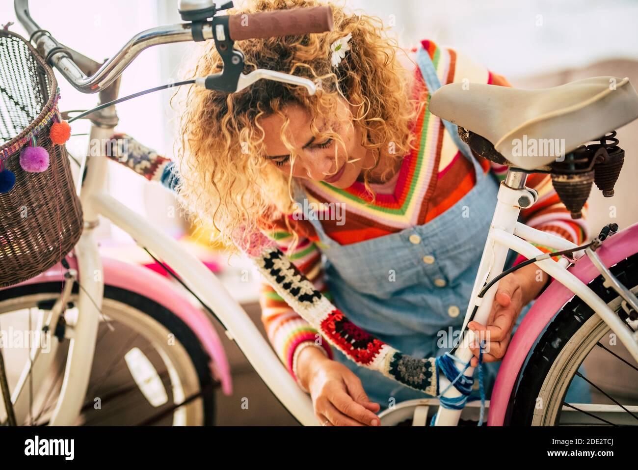 Belle femme adulte faire bricolage réparation et restauration à la maison d'un vélo utilisant de la laine de couleur - concep tof personnes en intérieur, activités de loisirs en verrouillage Banque D'Images