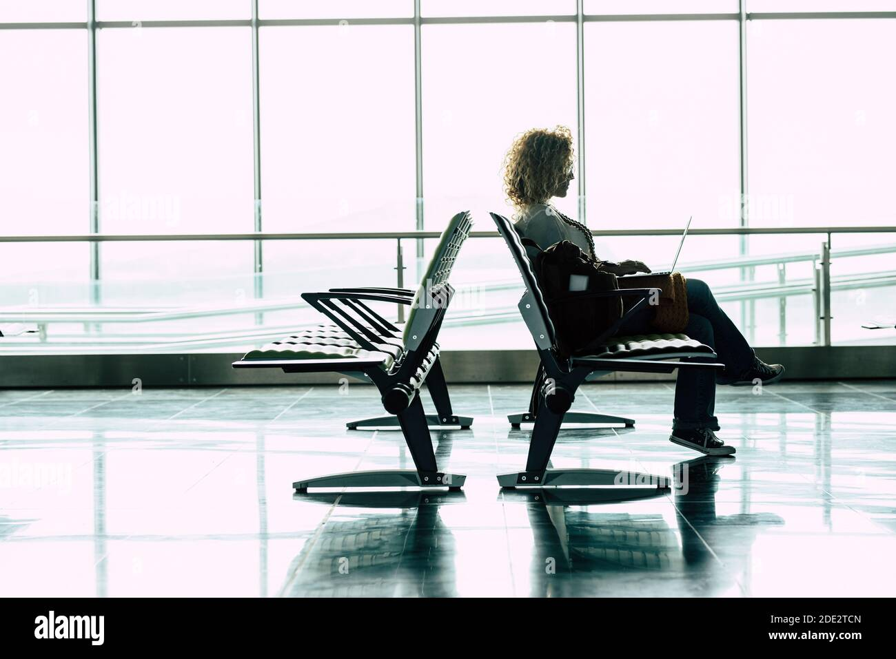 Déplacements et travail en ligne des employés à la porte de l'aéroport - la femme s'assoit et attend son vol avec ordinateur portable en mode travail intelligent ou nomade numérique Banque D'Images