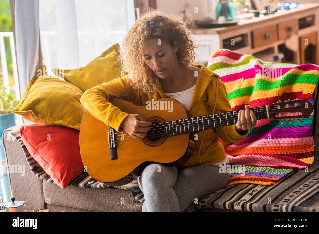 Jeune femme adulte à la maison apprenant à jouer de la guitare - people and music concept - belle femme jouant instrument assis sur le canapé pendant le verrouillage Banque D'Images