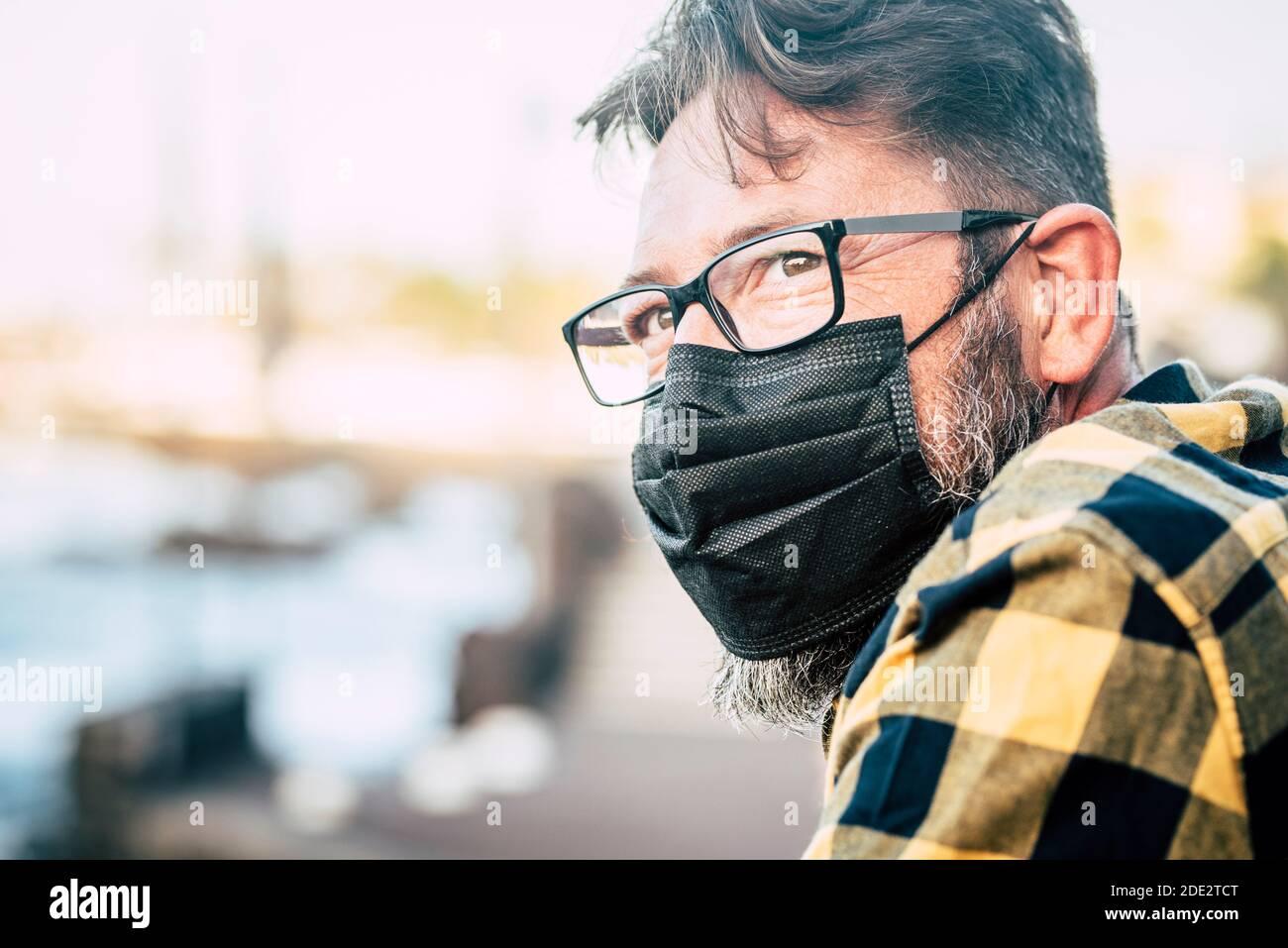 Gros plan portrait d'un beau homme avec un masque médical et des gloses pour protéger contre l'urgence pandémique covid-19 du coronavirus - personnes et mesures de sécurité Banque D'Images
