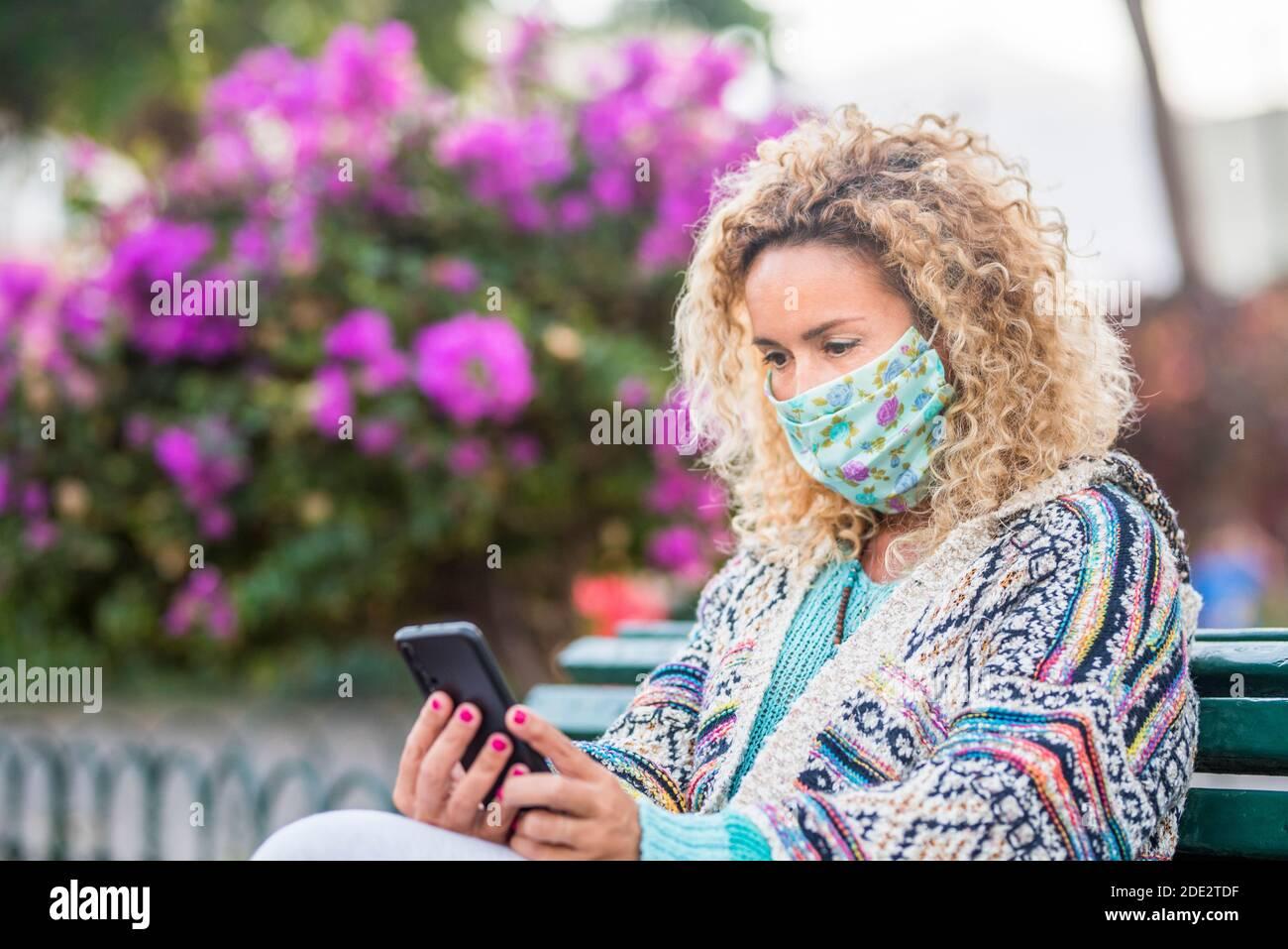 Adultes avec masque médical facial pour l'urgence du coronavirus covid-19 protection extérieure - une femme regarde le téléphone pendant une urgence covid-19 Banque D'Images