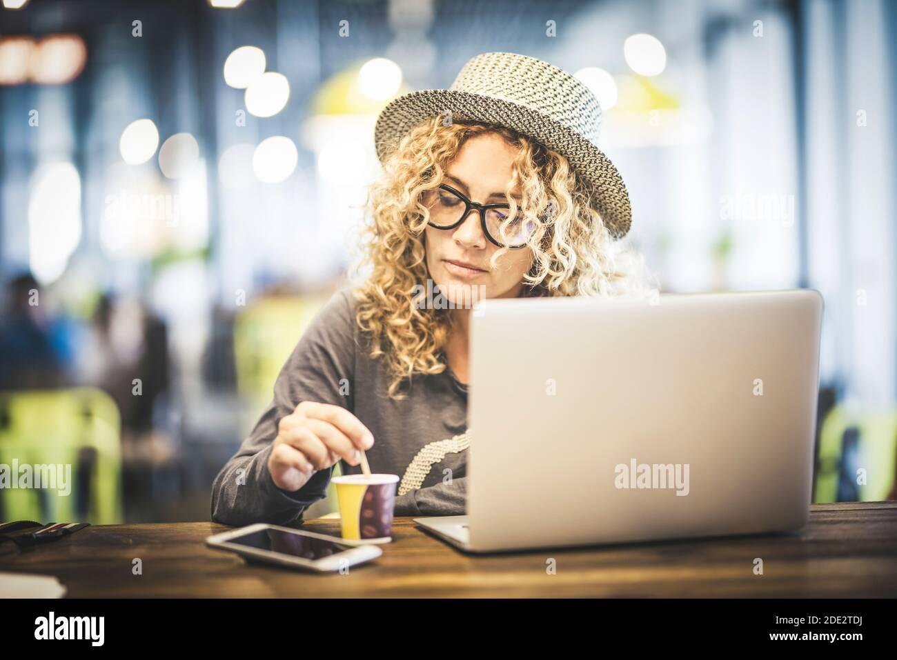 Belle jeune femme adulte au travail avec ordinateur portable coimputer dedans un café restaurant à l'aéroport en attente de son vol pour voyager - numérique nomade et mod Banque D'Images