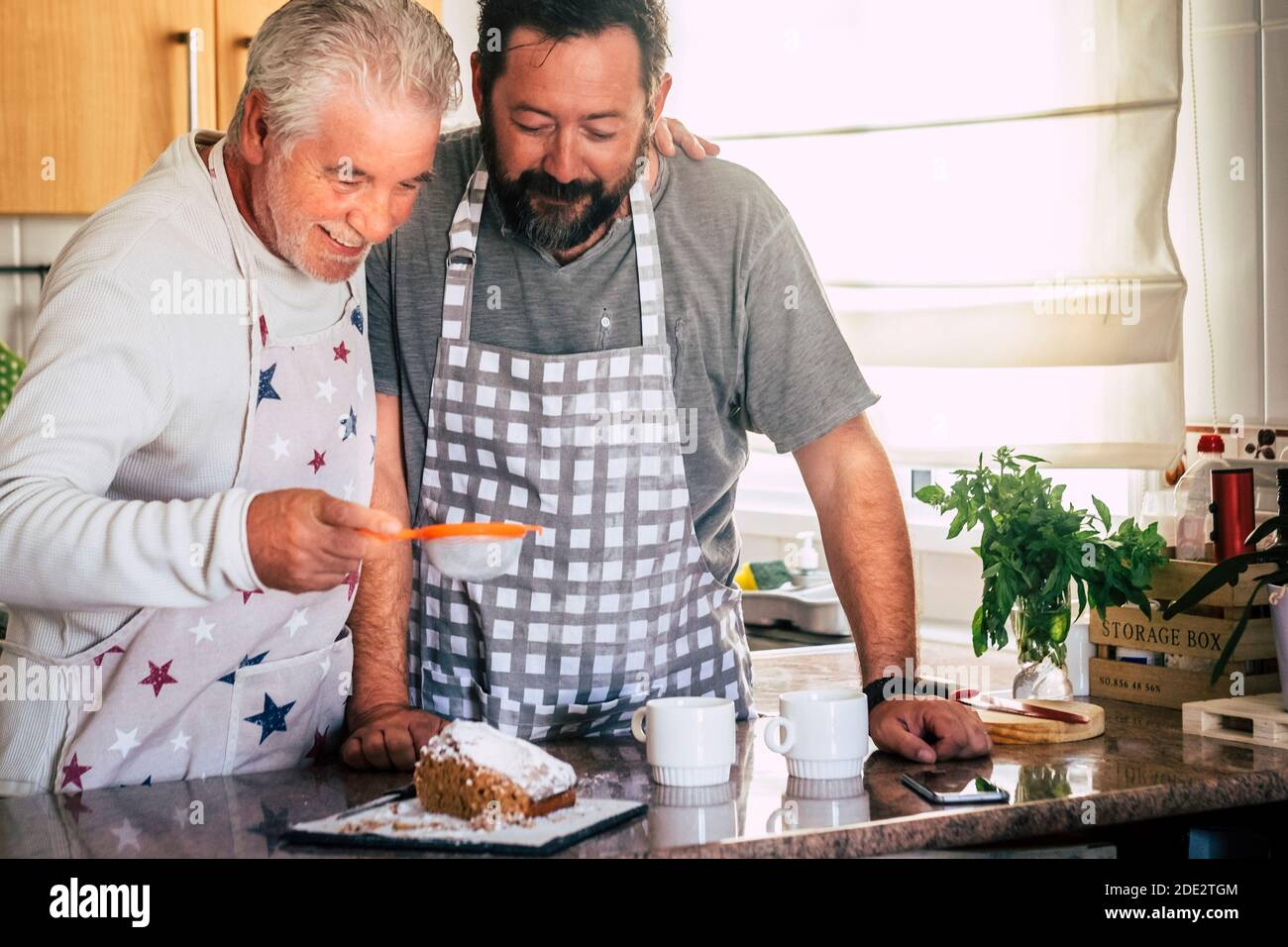 Couple d'adultes et d'hommes âgés père et fils ou les amis cuisent ensemble à la maison dans la cuisine en s'amusant - activité de boulangerie à la maison avec différents âges Banque D'Images