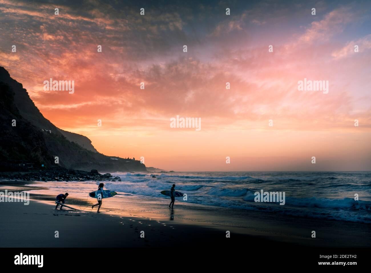 Un coucher de soleil aux couleurs incroyables sur la plage avec groupe de surfeurs aller à l'eau - sport de l'océan en été vacances pour les personnes actives Banque D'Images