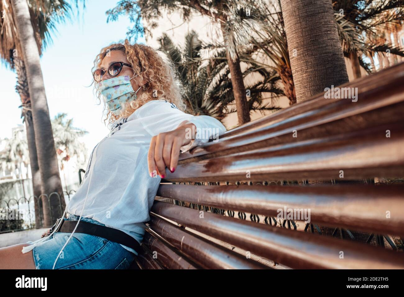 Une femme s'assoit sur un banc portant un masque médical pour les épidémies de protection du coronavirus covid-19 - concept de restrictions extérieures pour lutter contre la pandémie Banque D'Images