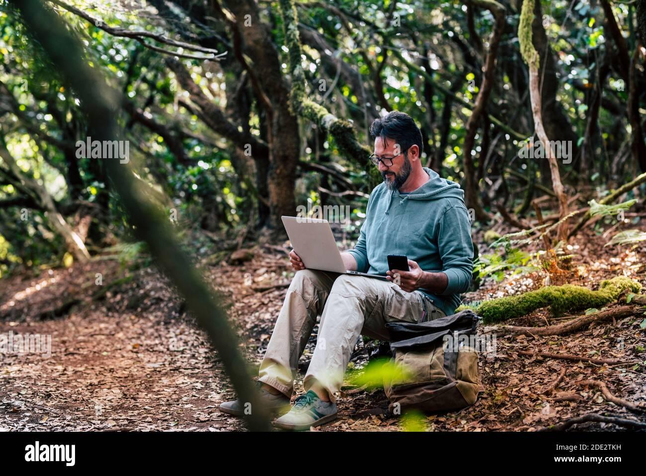 Adulte jeune homme travaille avec la technologie de connexion en itinérance en ligne en extérieur avec téléphone et ordinateur portable - les gens dans la nature à l'extérieur bureau alternatif avec Banque D'Images