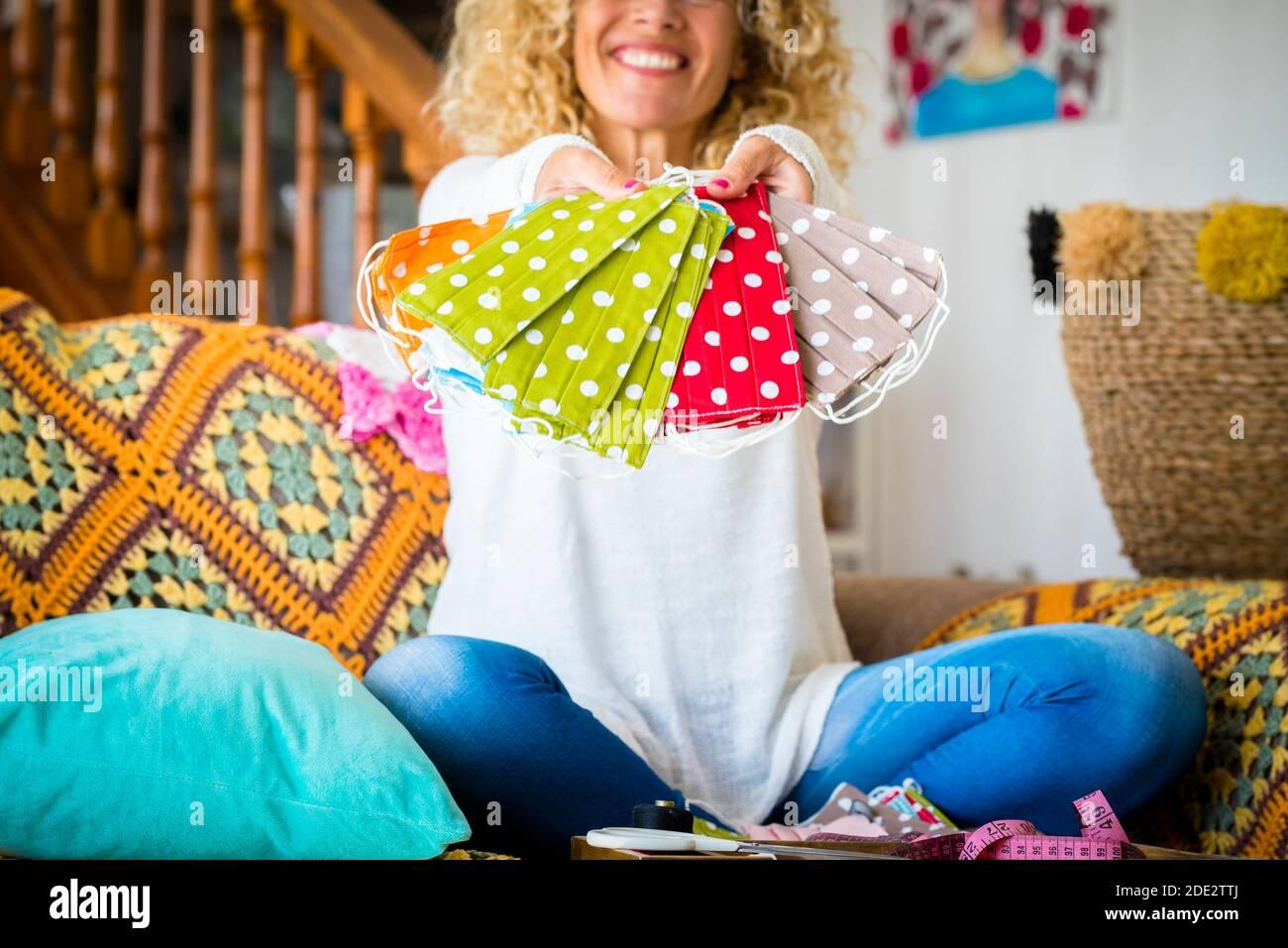 Une femme joyeuse à la maison montre sa main fait la mode tendance masque facial pour la protection du coronavirus covid-19 pendant les restrictions de verrouillage d'urgence Banque D'Images